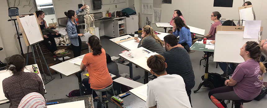 classroom of students sitting at easels learning about drawing anatomy