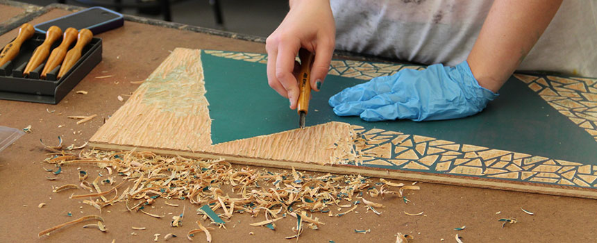 student working on a wood carving
