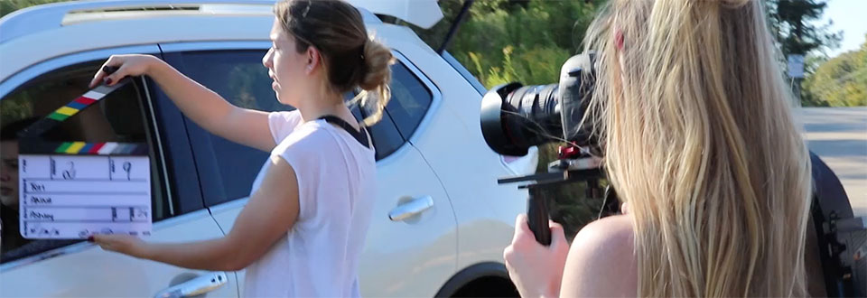 Students working with Canon equipment and shoulder mounts during an in-car scene