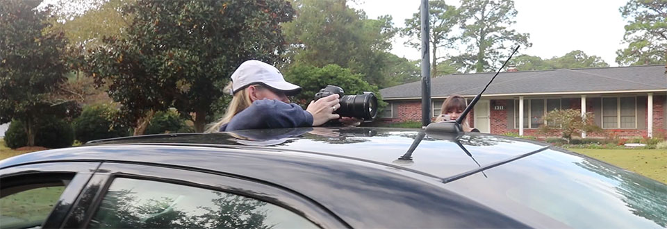 Student filming a walking scene from a moving car out of a sunroof