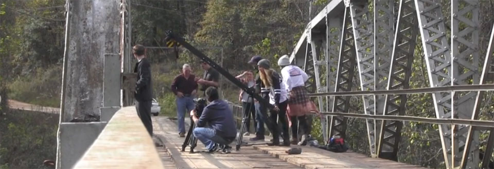 Students filming senior project on bridge with a jib and canon equipment