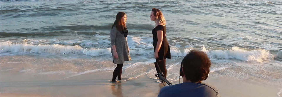 Recording natural audio sounds of crashing waves and two actors talking on a beach location