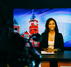 student conducting a newscast in front of a camera