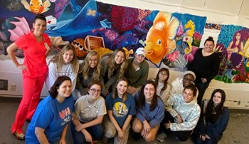 art students posed in front of colorful mural
